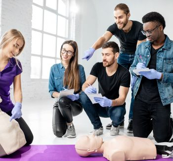 Group of young people learning to make artificial breathing with medical dummies during the first aid training in the white room